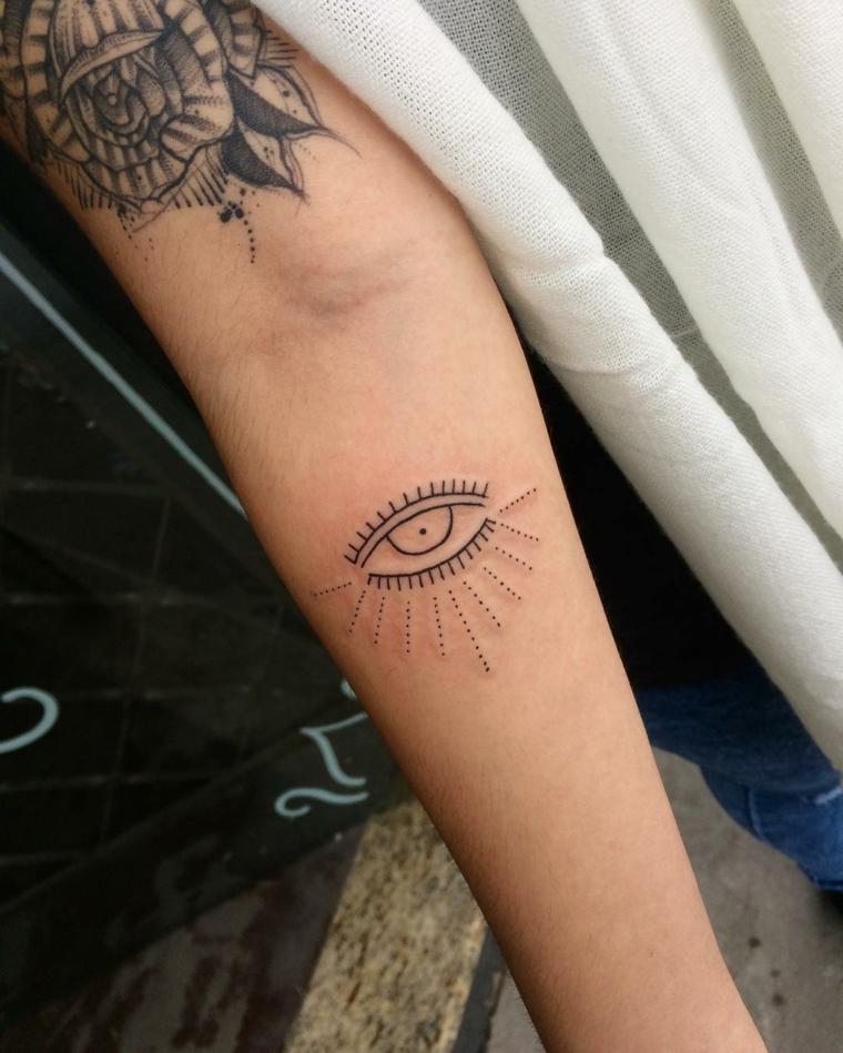 Tatuaggio illuminati, tatuaggio sull'avambraccio di una donna con disegno occhio e puntini