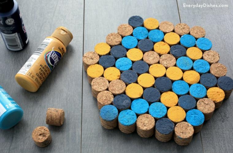 Sottobicchiere con tappi di sughero, bottiglie di vernice acrilica, materiali su un tavolo di legno