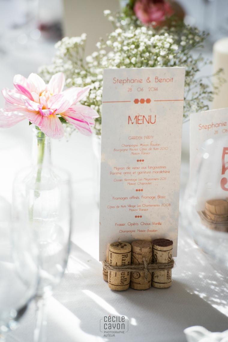Foglio con il menu in mezzo a dei tappi delle bottiglie, idee con tappi di sughero
