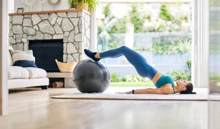 Donna che si allena su una palla di fitness, workout a casa su un tappeto morbido