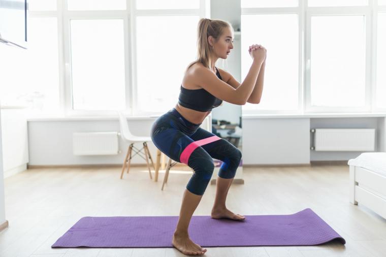 Esercizi da fare a casa, donna in posizione squat con elastico per le gambe