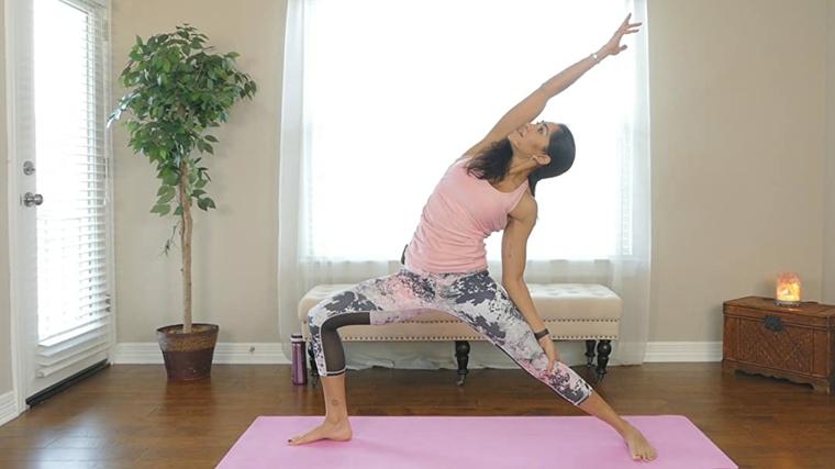 Donna in posizione di guerriero di yoga, allenarsi a casa donne, donna su un tappetino rosa