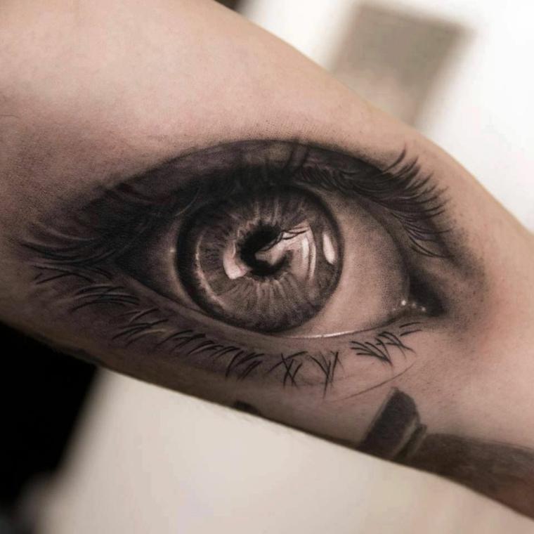Occhio tattoo old school, tatuaggio sull'avambraccio di un uomo