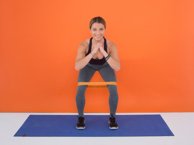 Workout a casa, donna in posizione di squat con un elastico, tappeto blu e parete arancione