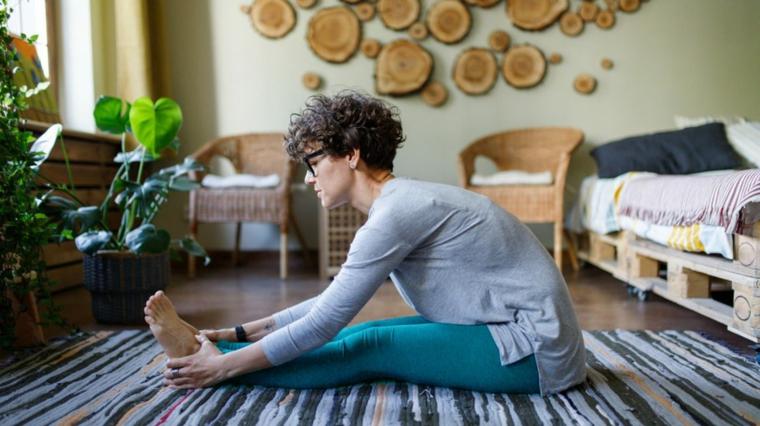 Allenamento gambe a casa, donna sul tappetino della camera da letto