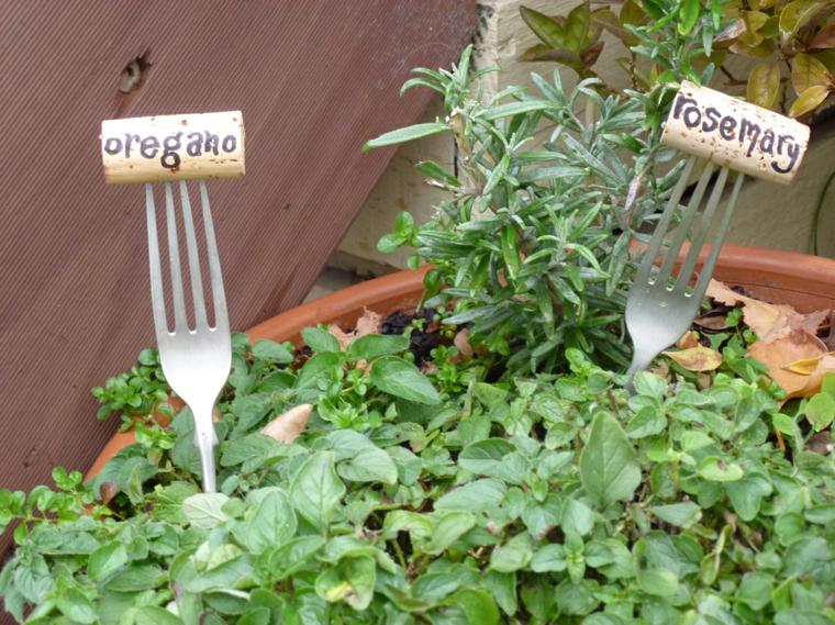 Vaso con piante aromatiche, tappi di sughero con scritte su due forchette