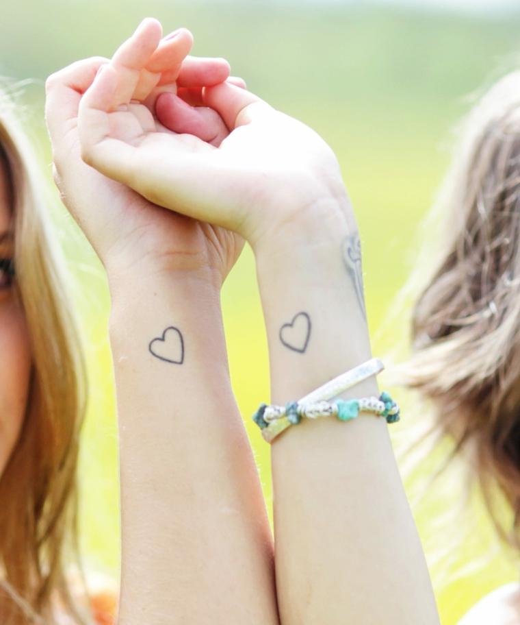 Tatuaggio simbolo amicizia, tattoo sul polso della mano con disegno di due cuori