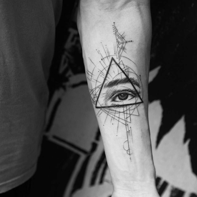 Occhio di ra significato, uomo con tatuaggio sull'avambraccio con disegno triangolo e occhio