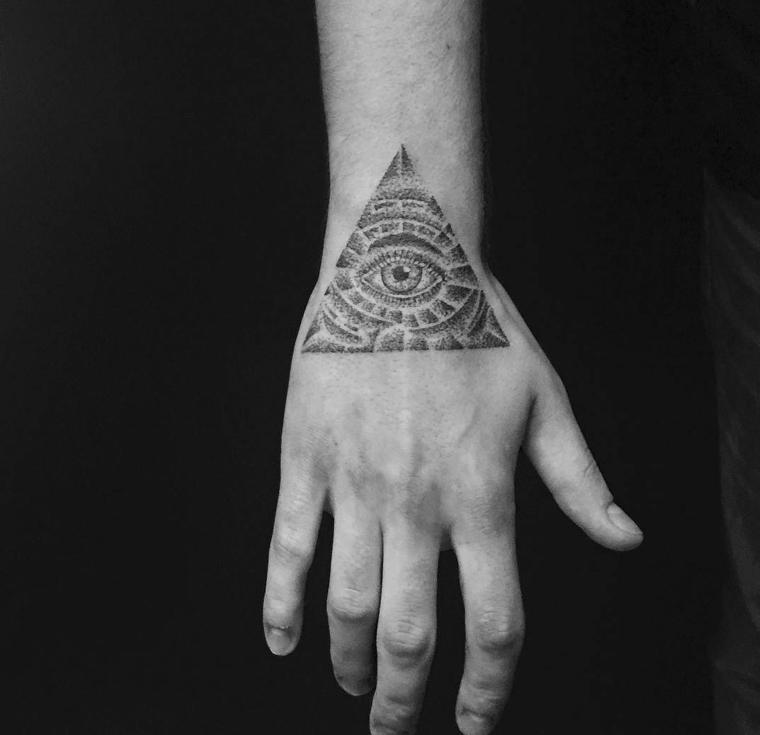 Occhio tattoo old school, uomo con un tatuaggio sulla mano con disegno occhio in un piramide