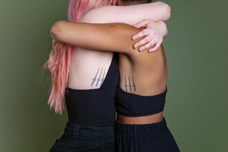 Tattoo migliori amiche, tatuaggio disegno pugnale sulla pancia di due ragazze abbracciate