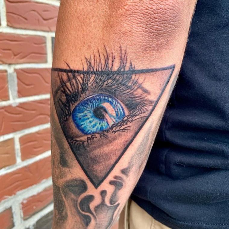 Tatuaggio occhio, uomo con un tattoo colorato sul braccio, disegno tatuaggio disegno occhio in un triangolo