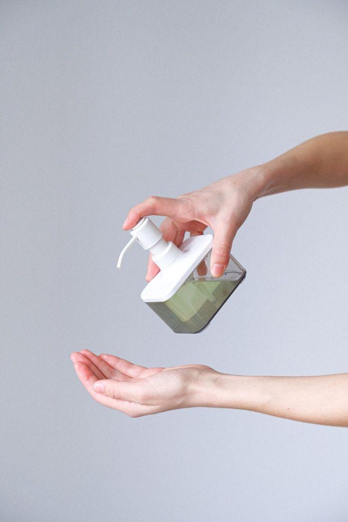 Donna che si versa del sapone sul palmo della mano, tutorial disinfettante mani