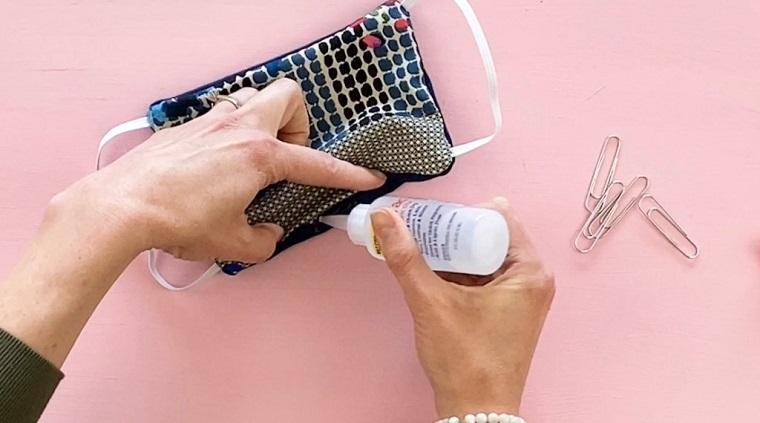 Donna che incollati pezzi di stoffa, tutorial come realizzare una mascherina di stoffa