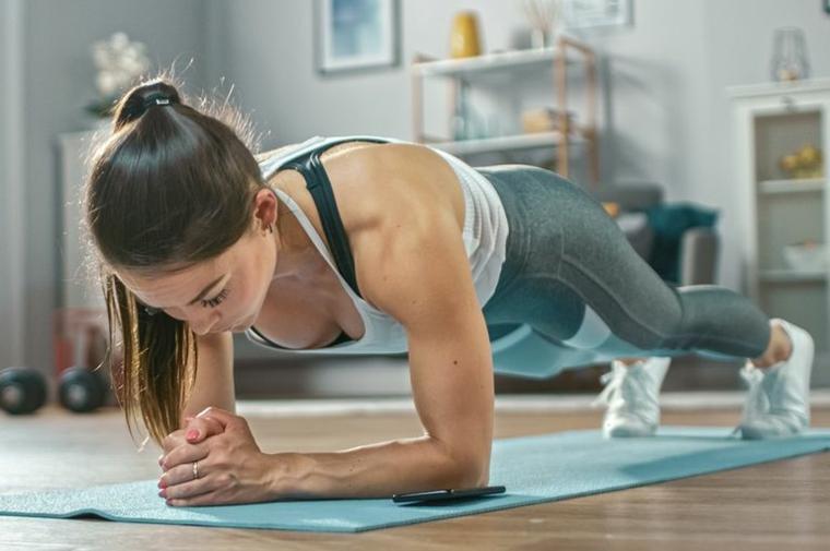 Donna in posizione di plank su un tappetino, allenamento a casa