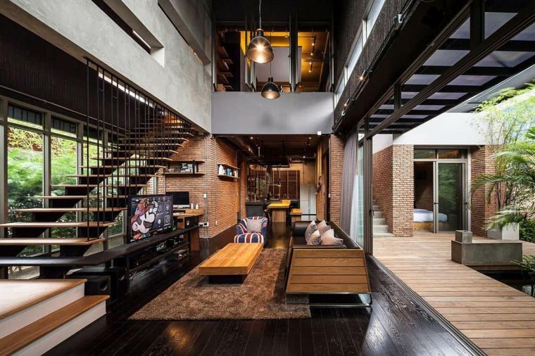 Ambiente open space con scale interne, soggiorno con divano in pelle e tavolino di legno