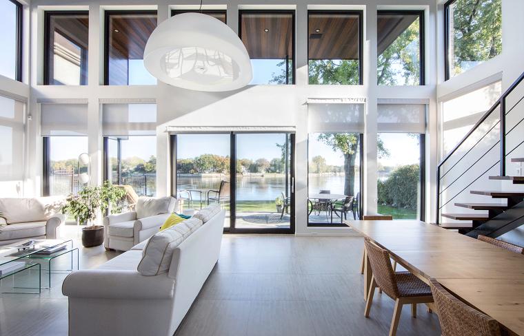 Ambiente loft con scale interne, soggiorno con divano e tavolino di vetro