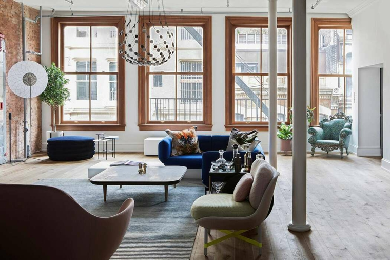 Pareti con mattini a vista e finestre, soggiorno con divano e tavolino basso, come arredare un loft open space