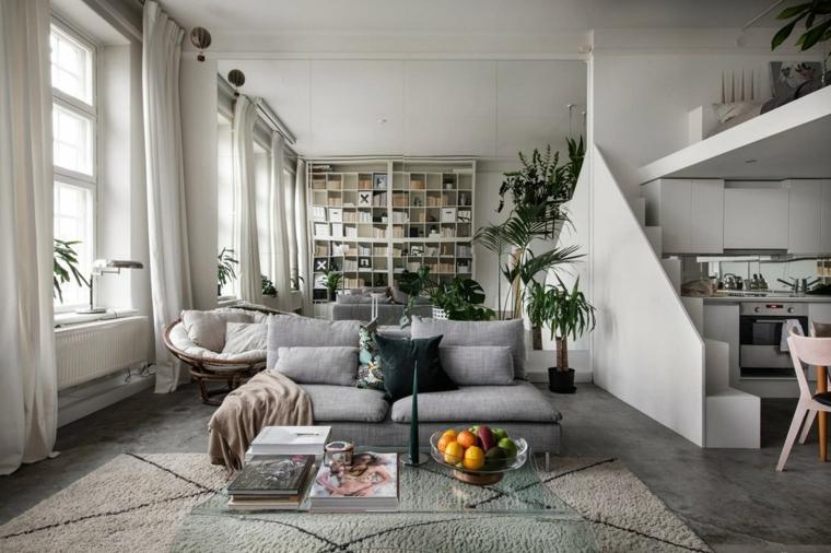 Open space con soppalco, soggiorno con divano e tavolino in vetro, camera da letto sul soppalco
