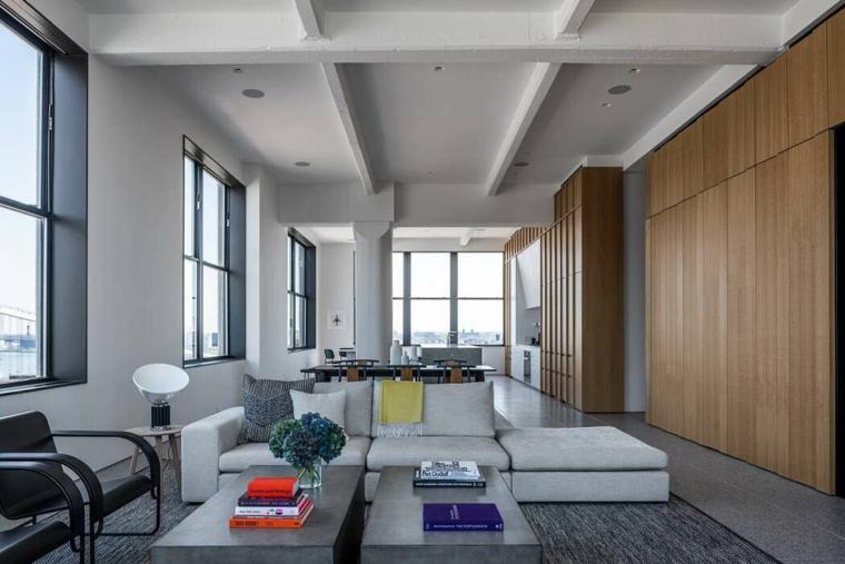 Come arredare un open space, soggiorno con divano e tavolini bassi, parete con pannelli di legno