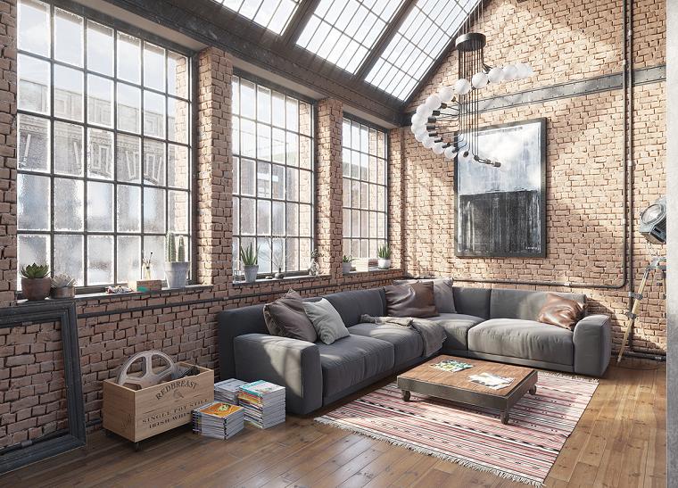 Arredare un loft, soggiorno con divano angolare e tavolino basso, parete con mattoni e finestre