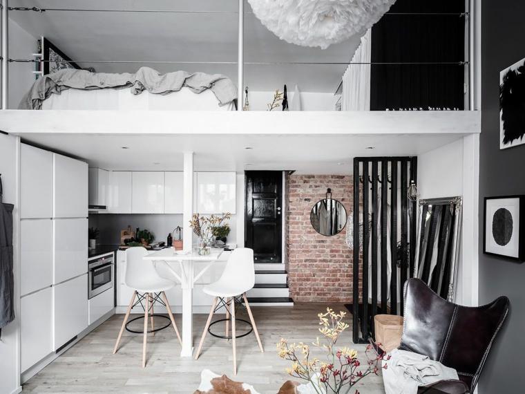 Open space con soppalco, cucina con tavolo da pranzo, parete con mattoni a vista