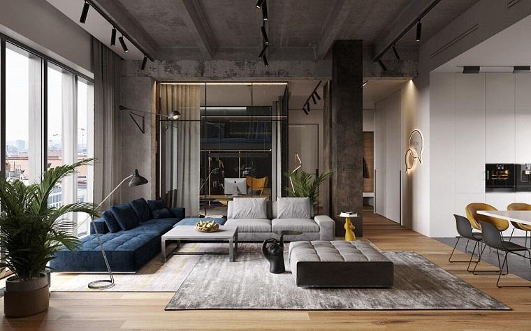 Open space con soppalco, loft con divano e tavolo da pranzo, soffitto in cemento con faretti