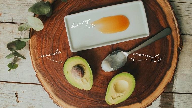 Maschera nutriente fai da te, tagliere di legno con avocado e miele