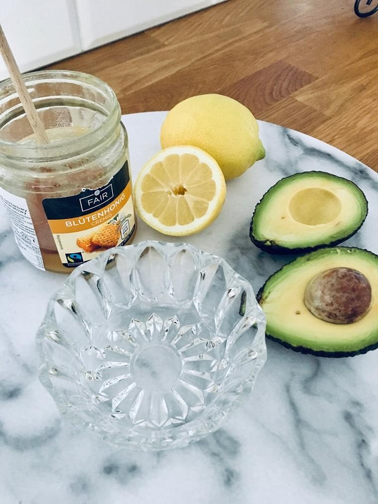 Come riparare i capelli danneggiati, tavolo con avocado e un barattolo di miele