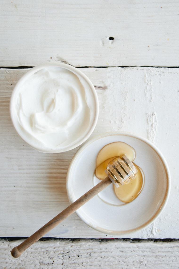 Maschera nutriente fai da te, due ciotole con yogurt e miele, ingredienti in due ciotole