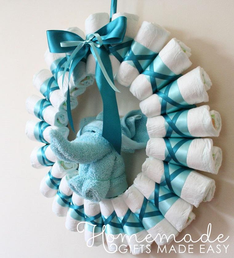 Fiocco nascita fai da te, corona con pannolini e nastro azzurro accanto ad un elefante peluche