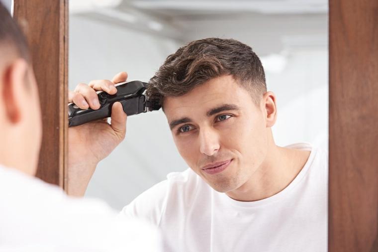 Sfumatura taglio capelli uomo, ragazzo che taglia i capelli con la macchinetta di fronte ad uno specchio