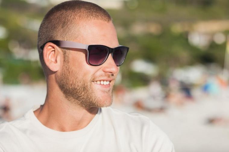 Tagli di capelli corti uomo, ragazzo sorridente con occhiali da sole, acconciatura capelli rasati