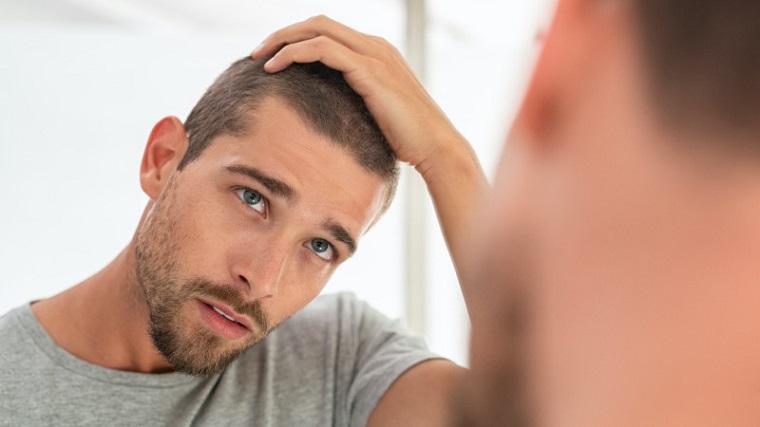 Come si tagliano i capelli, uomo con la mano tra i capelli, uomo che si guarda allo specchio