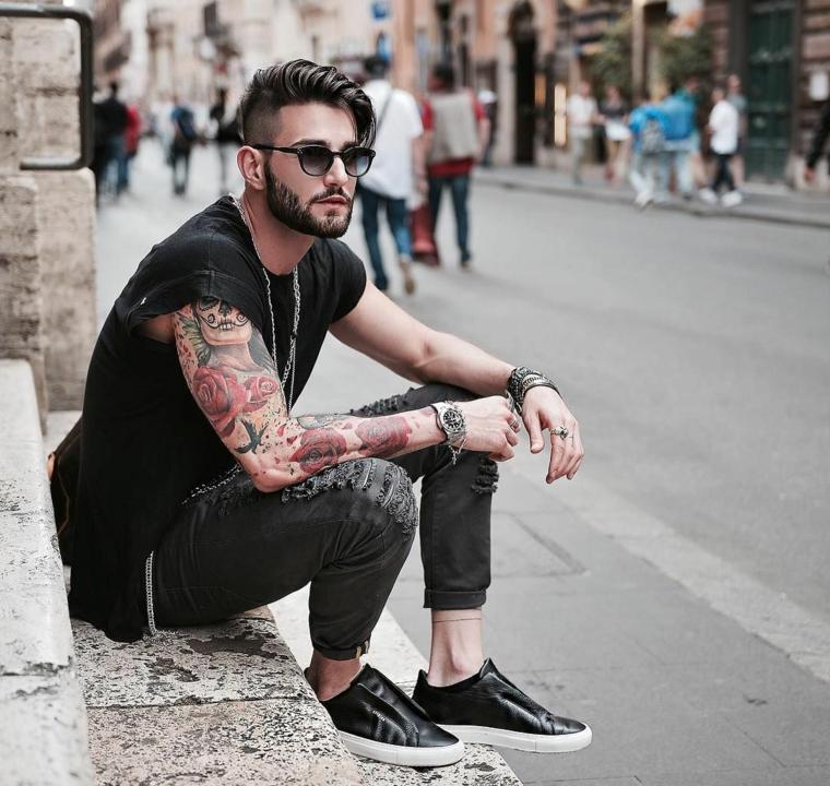 Uomo con tatuaggi sul braccio, taglio capelli uomo corti, acconciatura lunghi sopra e rasati ai lati