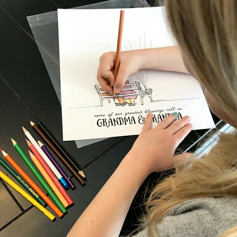 Biglietto festa dei nonni, bambina che colora con le matite un disegno dei nonni