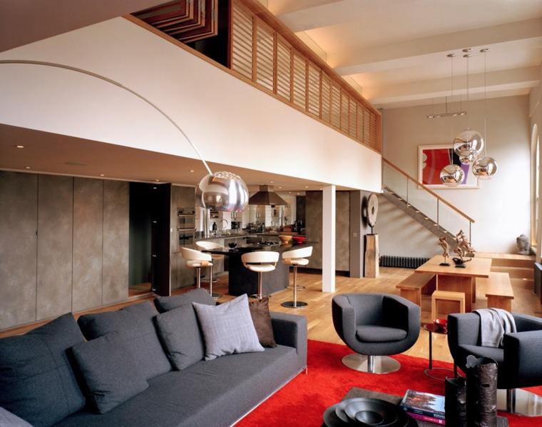 Appartamento con soppalco, soggiorno con divano, sala da pranzo con tavolo di legno e panchine