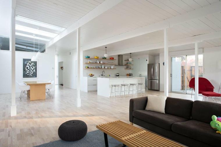 Cucina open space con isola centrale, appartamento loft luminoso, divano e panchina di legno