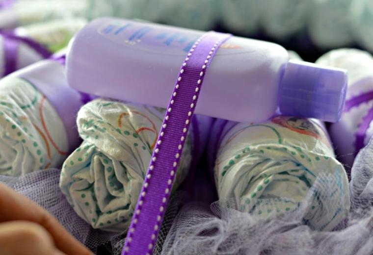 Bottiglia di crema corpo neonati, pannolini avvolti in nastro, coccarda nascita
