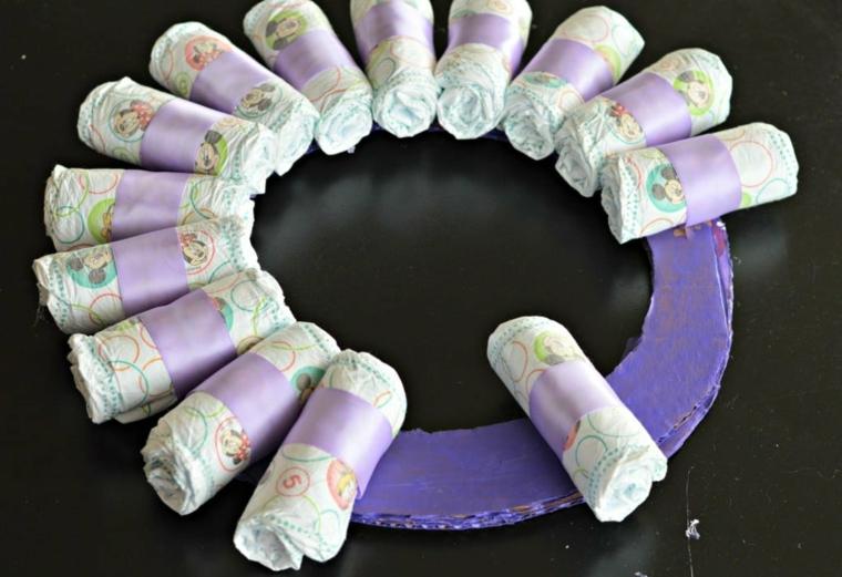 Cerchio di cartone dipinto di viola, pannolini avvolti in nastro, fiocchi nascita da esterno