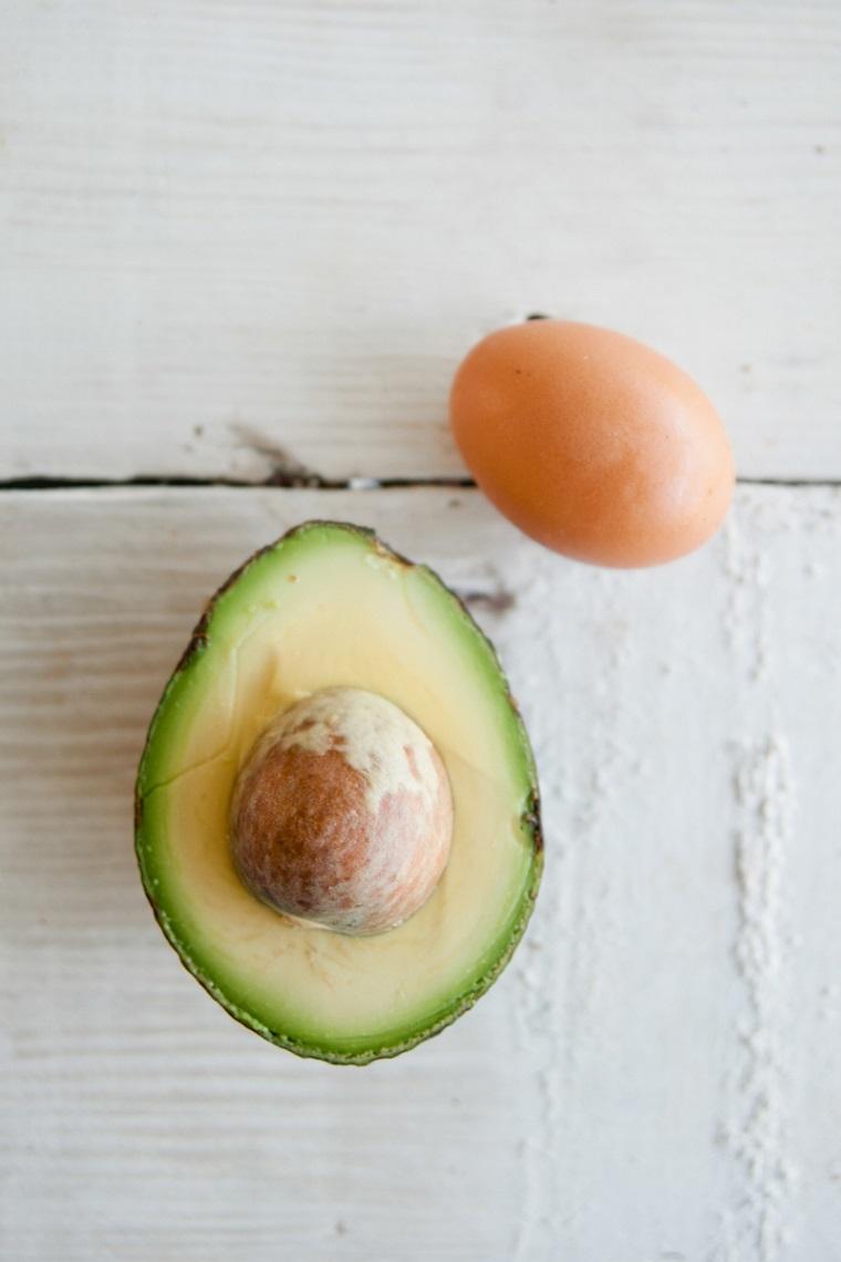 Maschere per fai crescere i capelli, ingredienti su un tavolo di legno, avocado tagliato e uovo