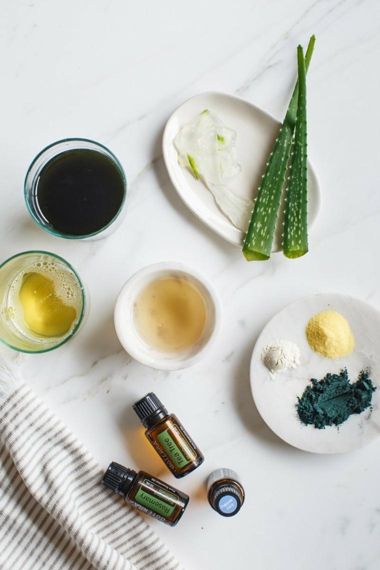 Bottigliette con olio essenziale, piatti con foglie di avocado, come riparare i capelli danneggiati