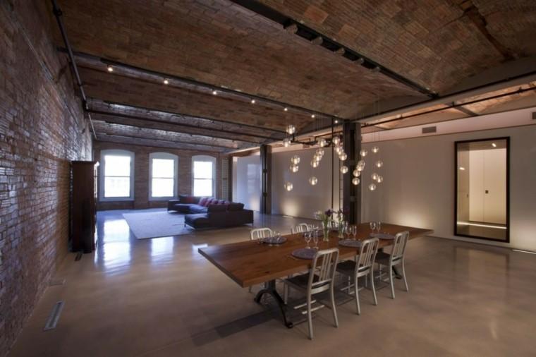 Stanza con pareti in mattoni a vista, soggiorno e sala da pranzo insieme, tavolo lungo con sedie