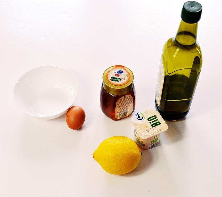 Maschera per capelli grassi, ingredienti su un tavolo bianco, limone e barattolo di yogurt