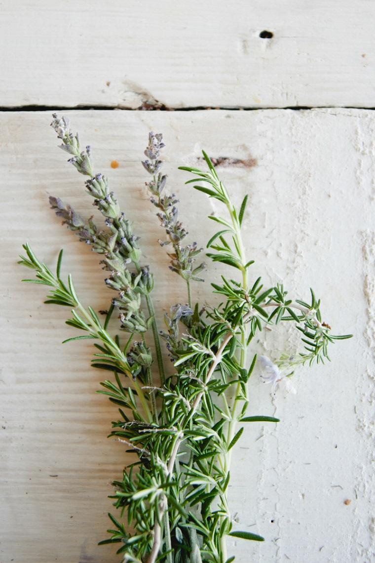Rametti di rosmarino e fiori di lavanda, come nutrire i capelli, ingredienti su un tavolo di legno