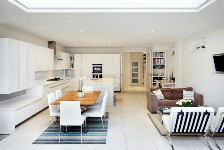 Cucina e sala da pranzo insieme, divano e tavolino basso, pavimento in piastrelle con tappetini