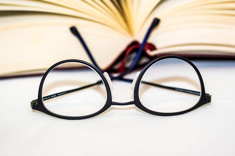 Occhiali da vista con montatura di colore nero, libro aperto e occhiali da vista