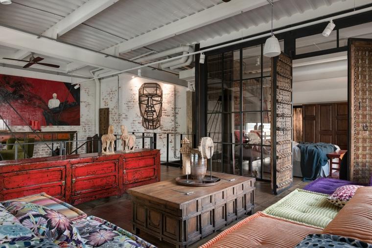 Appartamento open space significato, soggiorno con divano e tavolino, camera da letto a vista