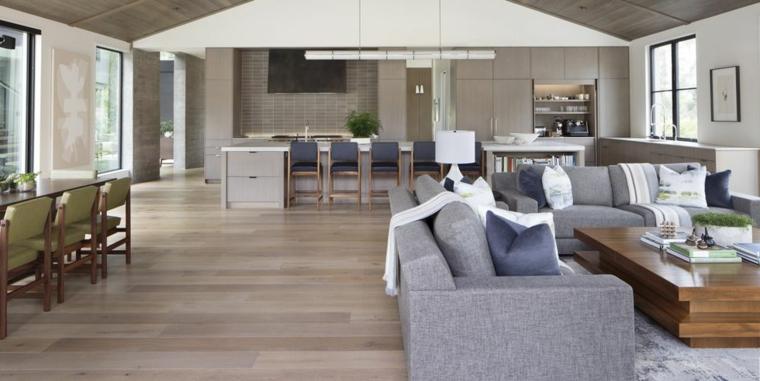 Zona living open space, soggiorno con divani e tavolino di legno, cucina con isola centrale