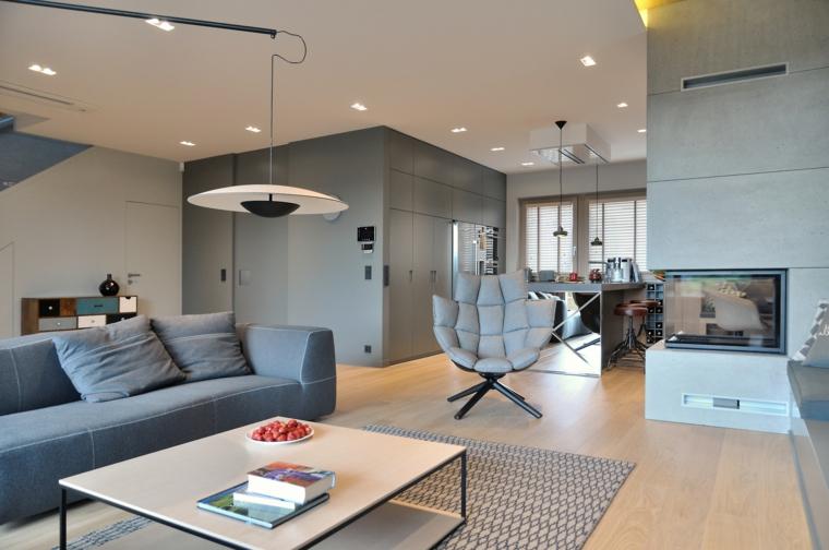 Soggiorno con divano grigio e tavolino basso, open space con cucina e sala da pranzo