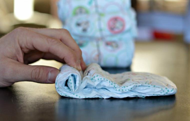 La mano di una donna che avvolge un pannolino, come fare un fiocco di tulle